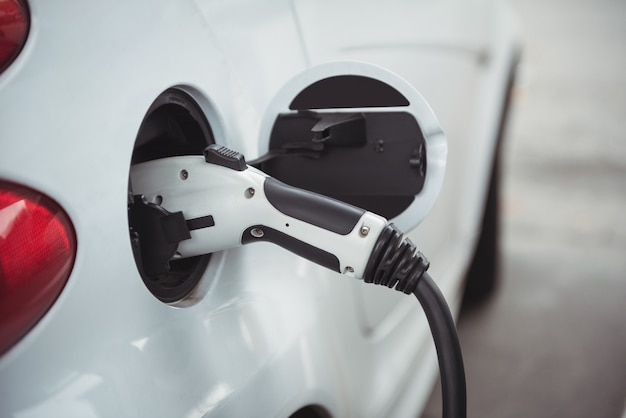 Close-up of car being charged with electric car charger Free Photo