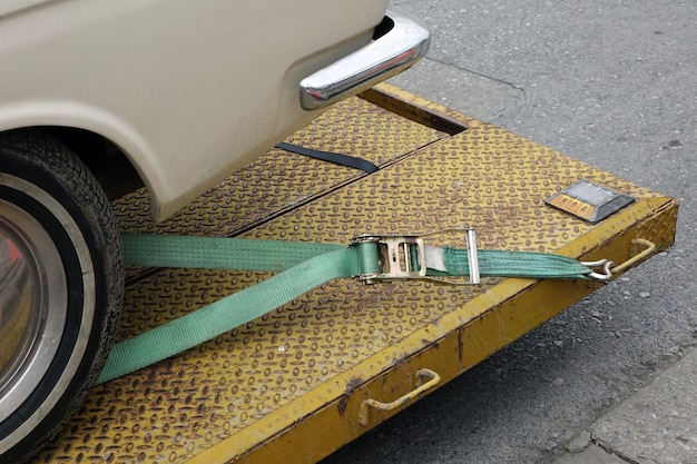 Close up of car hold with cable strap  on the tow truck.vehicle automobile problem concept. Premium Photo