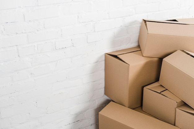 Close-up of cardboard boxes in front of white brick wall Free Photo