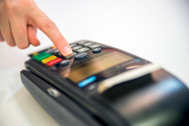 Close-up of cards servicing with pos-terminal, isolated on white background.female hand with credit card and bank terminal Free Photo