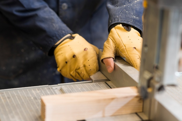 Close-up of a carpenter hands working with wooden block on workbench Free Photo