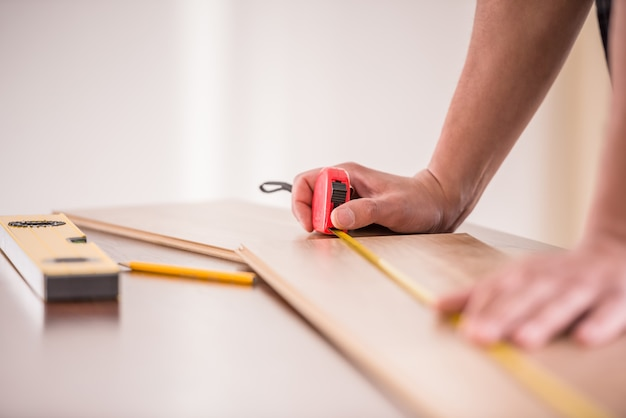 Close-up of carpenter measuring wooden plank. Premium Photo