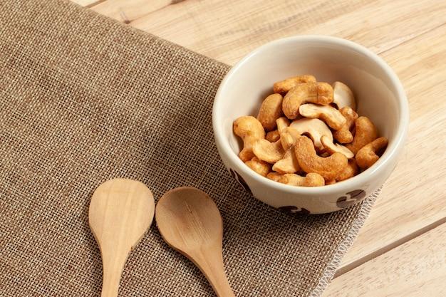 자루와 나무 테이블에 넣어 그릇에 캐슈 땅콩 건조 식품 스낵을 닫습니다 프리미엄 사진