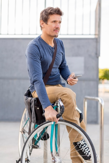 Крупный план случайный мужчина, закрепляющий свой велосипед Бесплатные Фотографии