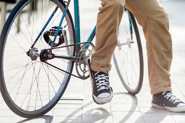 Крупный план случайный мужчина, сидящий на велосипеде Premium Фотографии