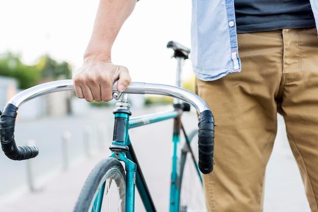 Крупный план случайный мужчина держит свой велосипед Бесплатные Фотографии