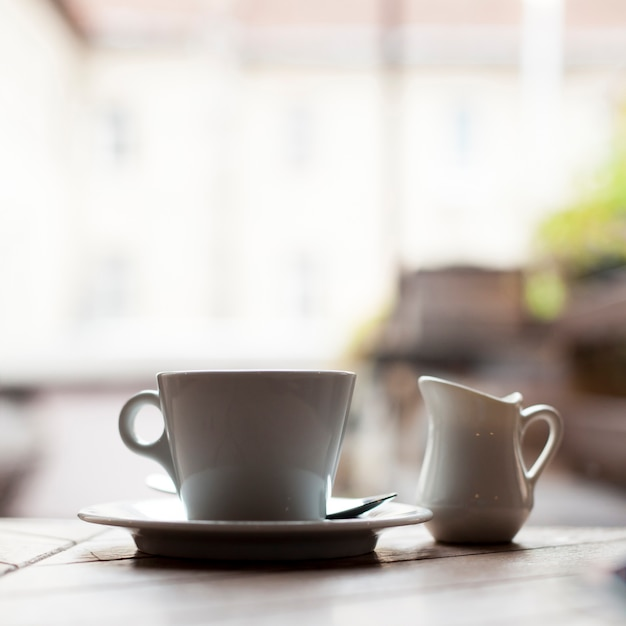 Close-up of ceramic coffee cup and milk pitcher Free Photo