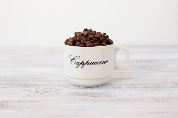 Close-up ceramic cup with coffee beans Free Photo
