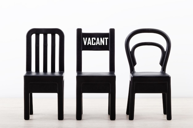 Close-up of a chair with text vacancy among black chairs in a row Premium Photo
