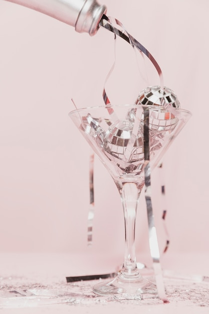 Close-up of champagne bottle pouring tinsel in glass Free Photo