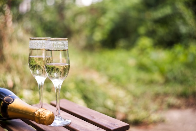 Close-up of champagne glasses on wooden table at outdoors Free Photo