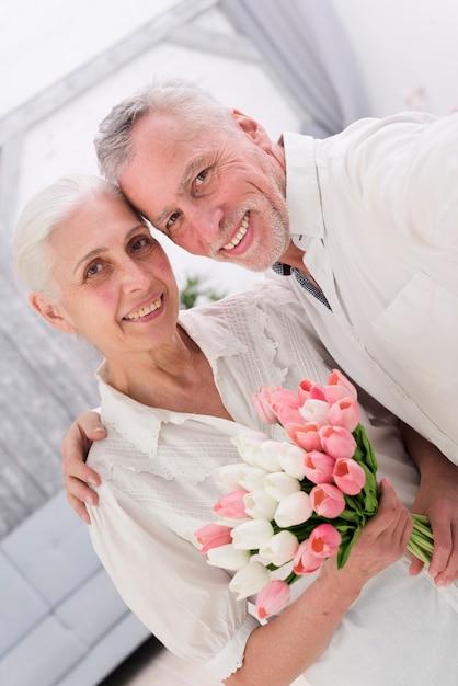 Il primo piano di una coppia anziana allegra con il bello tulipano fiorisce il mazzo Foto Gratuite