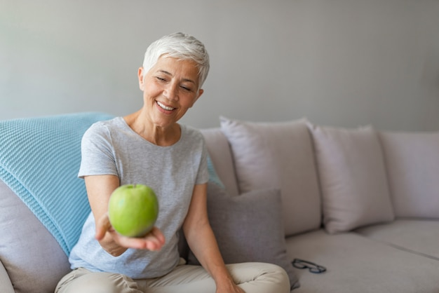 Close up of a cheerful elderly woman eating an apple while smiling at home. Premium Photo