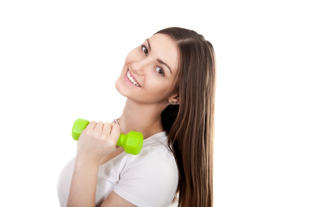 Close-up of cheerful girl posing with a green dumbbell Free Photo