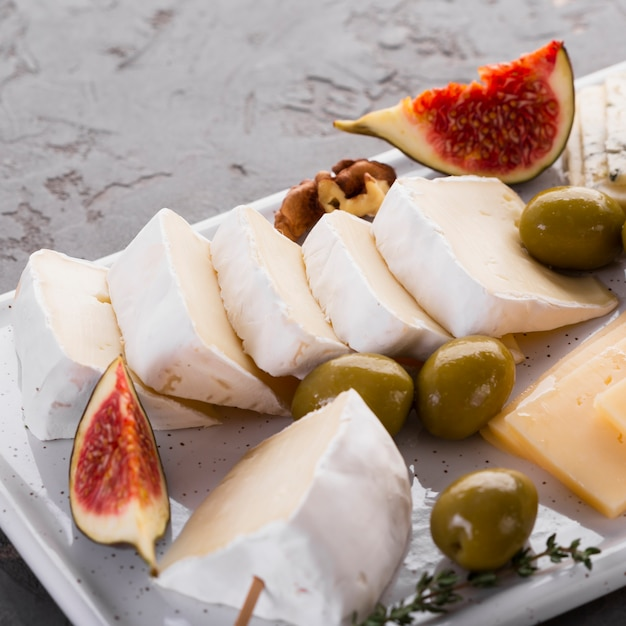 Close up cheese assortment platter with fig Free Photo