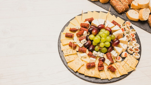 Close-up of a cheese platter with grapes and smoked sausages on slate board Free Photo