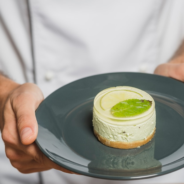 Close-up of chef's hand holding delicious dessert on reflective plate Free Photo