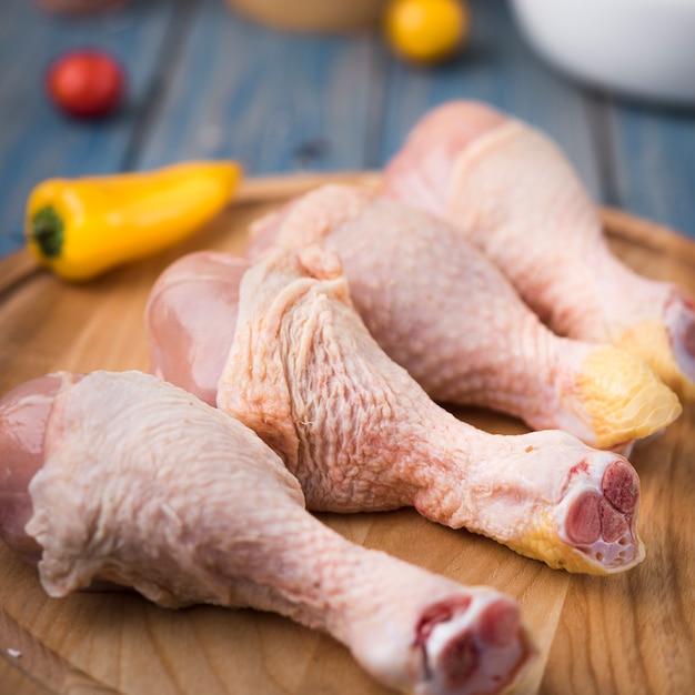 Close-up chicken drumsticks on wooden board with peppers Free Photo