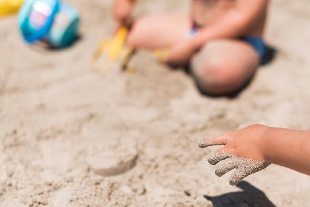 Chiuda in su delle mani del bambino che giocano con la sabbia in spiaggia Foto Gratuite