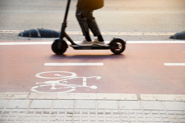 Close-up of a child riding kick scooter on cycle lane Free Photo