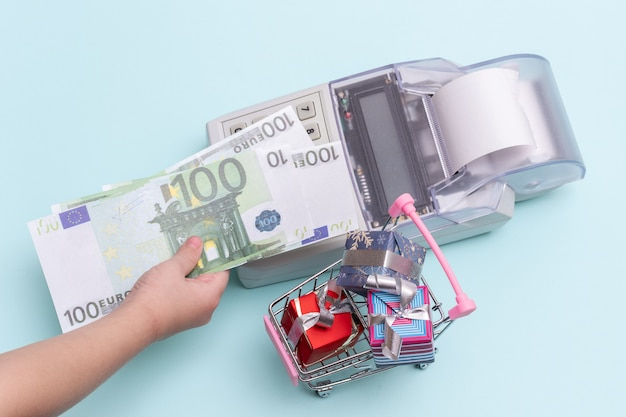 Close-up of a child's hand holding a copy of 100 euro banknotes above the cash register for buying boxes of gifts in a trolley Premium Photo
