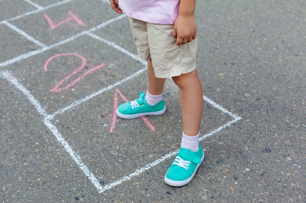 Close-up of childs legs and classics painted on asphalt. little girl playing hopscotch game on playground outside on a sunny day. Premium Photo