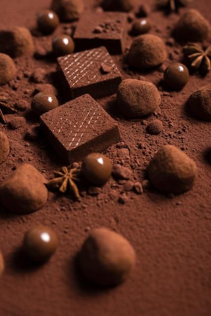 Chiuda sulle cialde e sui tartufi di cioccolato su cacao in polvere Foto Gratuite