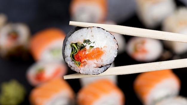 Bacchette close-up con rotolo di sushi Foto Gratuite