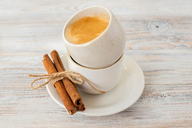 Close-up cinnamon sticks with coffee cups Free Photo