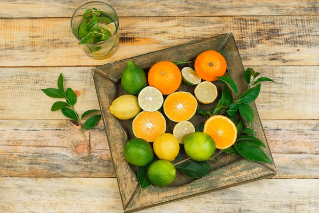 Close-up citrus fruits in bronze plate with fermented drink Free Photo