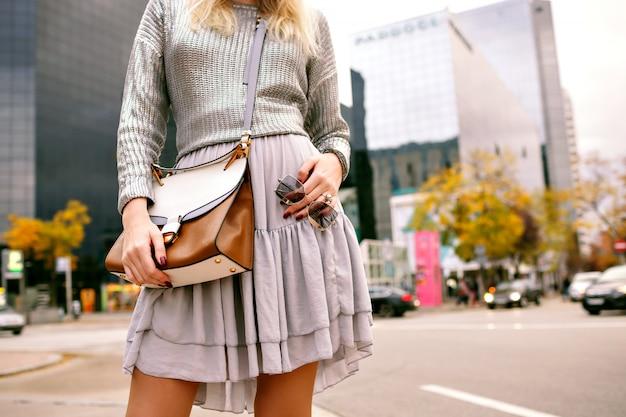 銀のセーター、シルクのスカート、高級革のバッグ、サングラスを身に着けているビジネスセンター、秋の春のシーズン近くのニューヨークのストリートでポーズをとってスタイリッシュなエレガントな女性の都市のファッションの詳細を閉じます。 無料写真