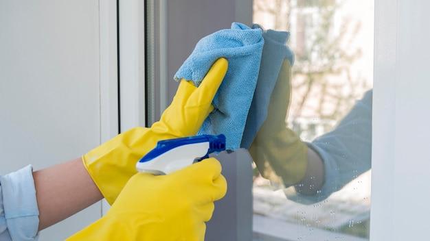 Очистка окна крупным планом с помощью химического спрея Premium Фотографии