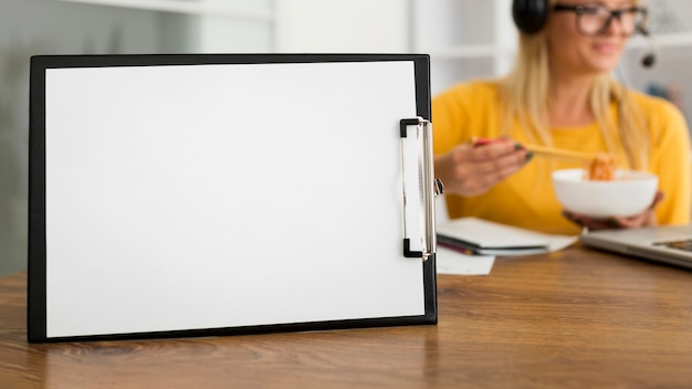 Close-up clipboard on the desk with woman behind Free Photo