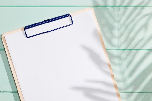 Close-up clipboard with copy space and shadow leaves Free Photo