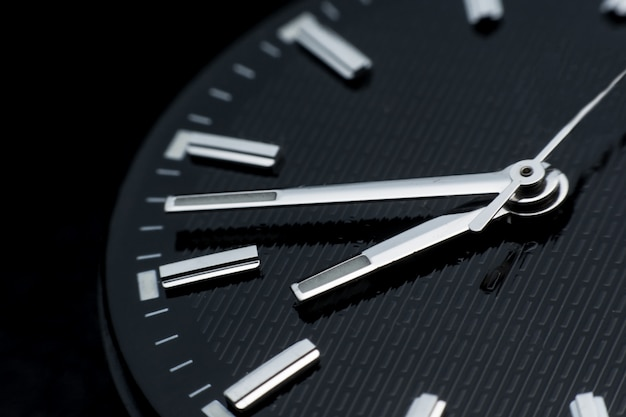 Close up clockwise on black clock face background. wristwatch in retro style Premium Photo