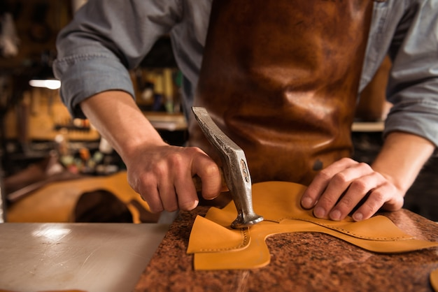 Close up of a cobbler working with leather Free Photo