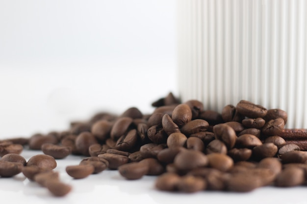 Close up coffee beans and white cup isolated on white background. Premium Photo