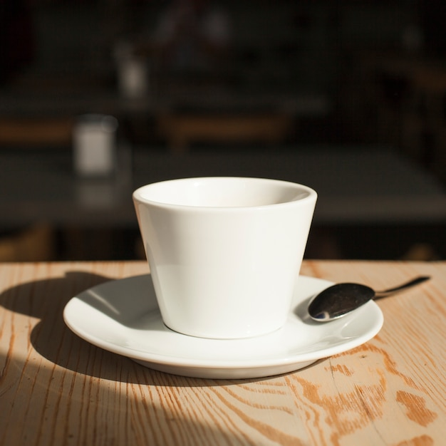 Close-up of coffee cup and spoon on desk Free Photo