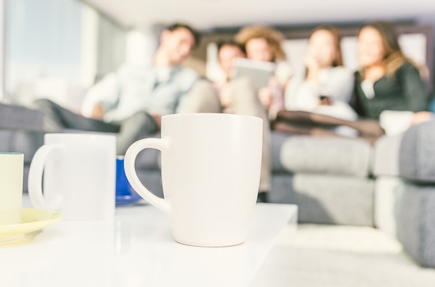 Close up on coffee cups in the living room with group of friends Premium Photo