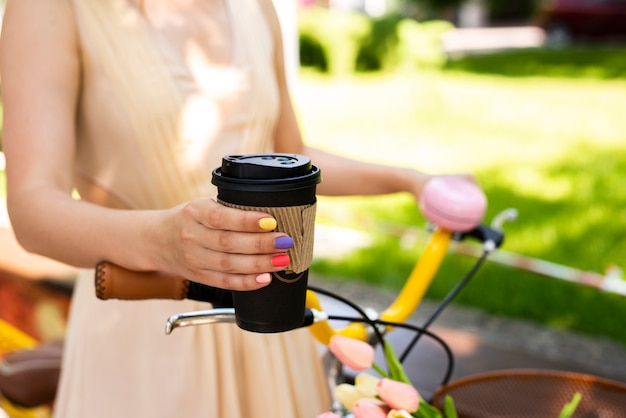 Close-up coffee hold by a stylish woman Free Photo