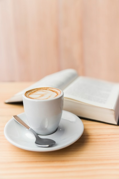 Close-up of coffee latte and open book on wooden table Free Photo