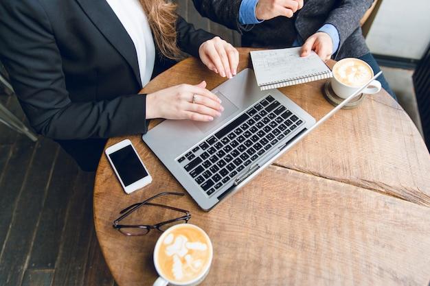 Primo piano di un tavolino da caffè con due colleghi seduti tenendo il taccuino e digitando sul computer portatile Foto Gratuite