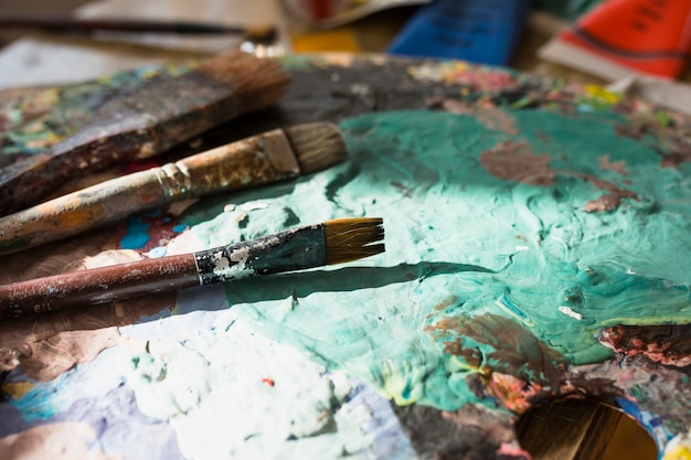 Close-up of colorful messy old paint brush and palette Free Photo