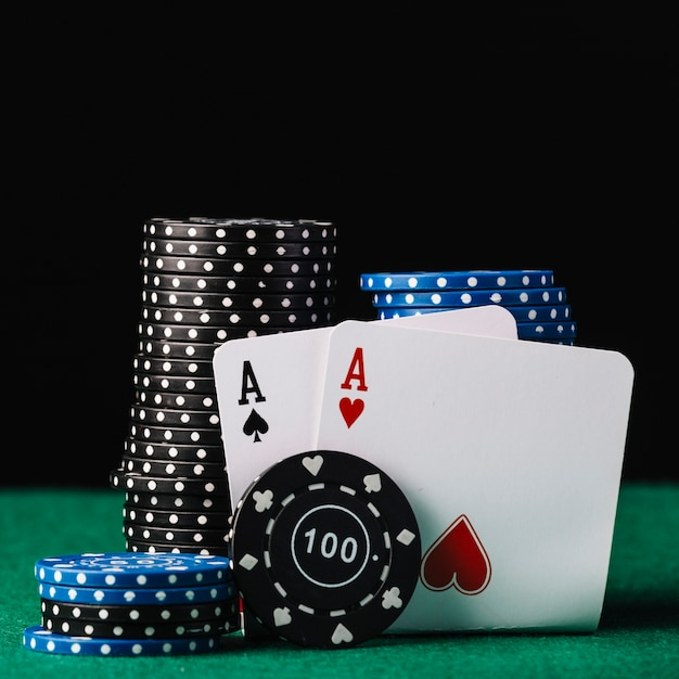 Close-up of colorful stacked casino chips with heart and spade aces on green table Free Photo