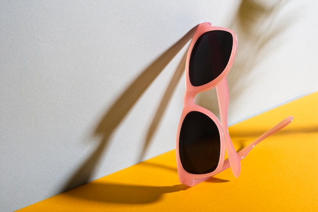 Close-up colorful sunglasses with shadow Free Photo