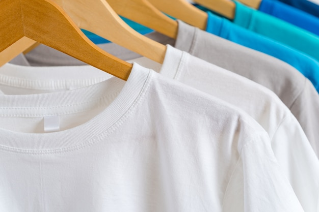 Close up of colorful t-shirts on hangers, apparel background Premium Photo