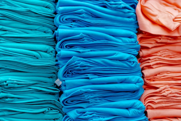 Close up of colorful t-shirts stacked on shelves Premium Photo