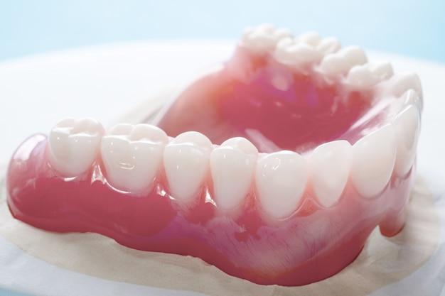 Close up , complete denture or full denture on blue background. Premium Photo
