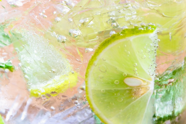 Close up concept on piece of lemon or lime in lemonade or mojito for wallpaper Premium Photo