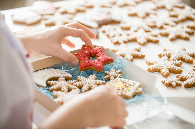 Close up of confectioner hand packing gingerbread cookies into b Free Photo
